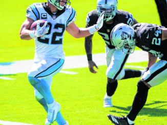 Carolina Panthers running back Christian McCaffrey scores ahead of Las Vegas Raiders safety Johnathan Abram during the second half of a game in Charlotte earlier this season.                                  Brian Blanco | AP File Photo