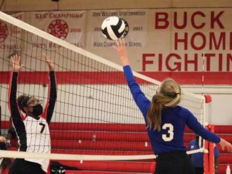 Senior Carleigh Carter tips a ball over the net as Hoke County's Faith Mason attempts to block it Monday night in Raeford.                                  Neel Madhavan | The Laurinburg Exchange