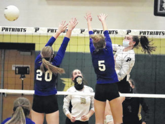 Junior Taylor Waitley (20) and junior Kate Carter (5) go up for a block Tuesday night against Pinecrest in Southern Pines.                                  Neel Madhavan | The Laurinburg Exchange